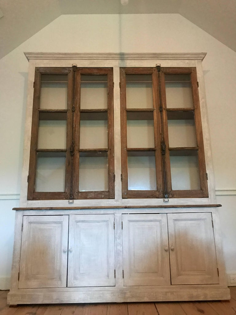 A two part French Provincial cabinet. Lower compartment have two double doors and interior shelves and the upper portion with shelving closed by two pairs of antique doors. Wonderful custom made piece repurposing antique hardware and doors.