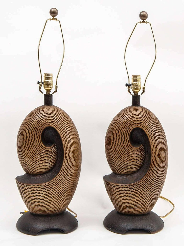 """Pair of Artmaster Studios ceramic lamps in shades of gold and black, signed. 21 """" H to the sockets; 10"""" H harps and finials included. Original wiring, with standard 3-way sockets in working condition. Age to metal parts."""