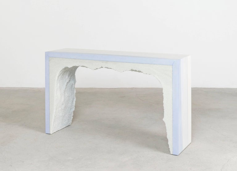 Composed from a combination of materials, the angular console consists of a hand-dyed ice blue cement exterior and a powdered glass interior. Packed by hand within the smooth ombre of cement, the white granules form an organic texture to contrast
