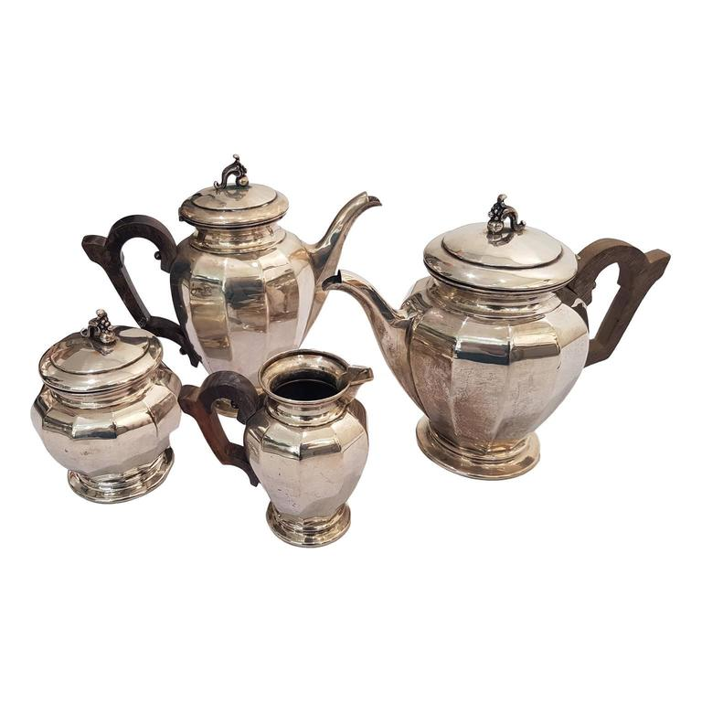 Set composed by teapot, coffee pot, milk jug and sugar bowl with wooden handle and hinged lids with cornucopia knobs.
