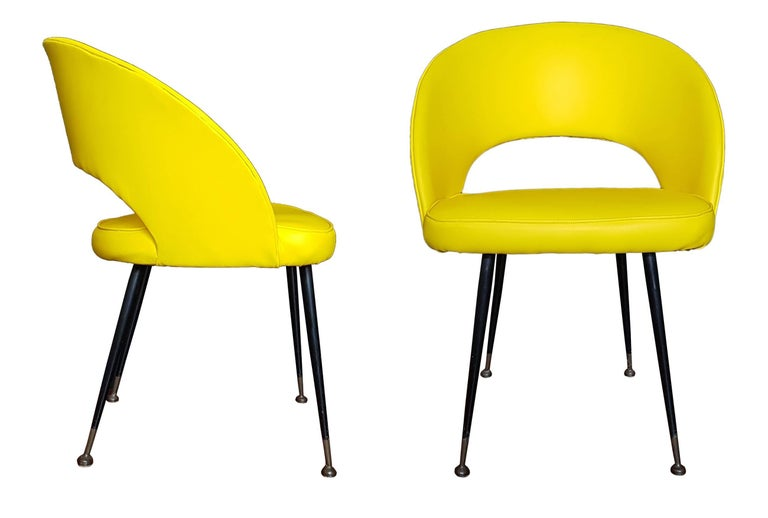 Couple of armchairs upholstered in yellow leatherette, legs of brass and steel tubs. Manufactured in the 1950s.