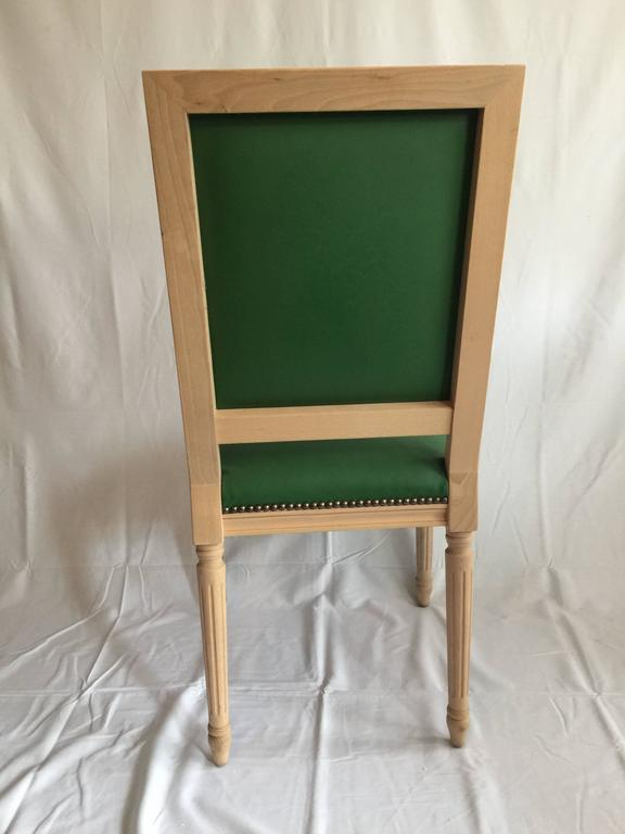 Square back Louis XVI style dining or side chair. Natural wood finish, custom colored Kelly green leather upholstery, antiqued brass nailhead detailing. Elegant carved details. 