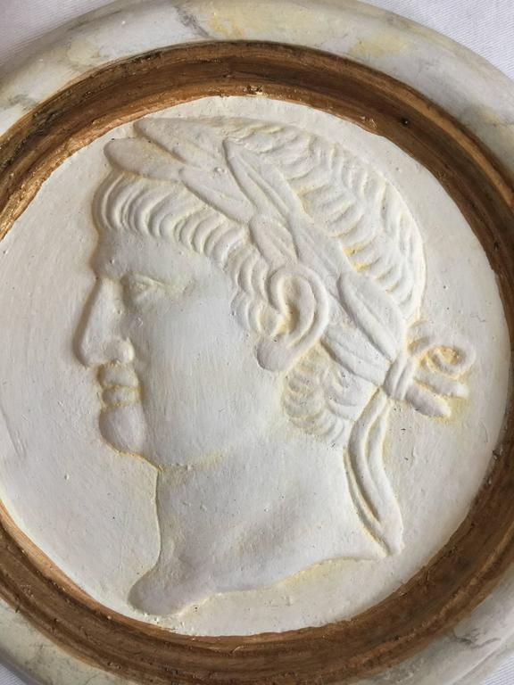 Handsome pair of Classic Roman reliefs or medallions. Marbleized detailing and painted gold finish. Cast plaster with wall hangers embedded in the material. Purchased in Rome.