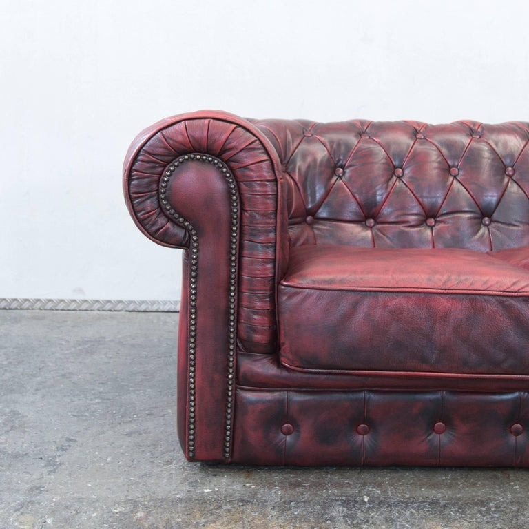Red colored Chesterfield designer leather sofa in a vintage style, designed for pure comfort.