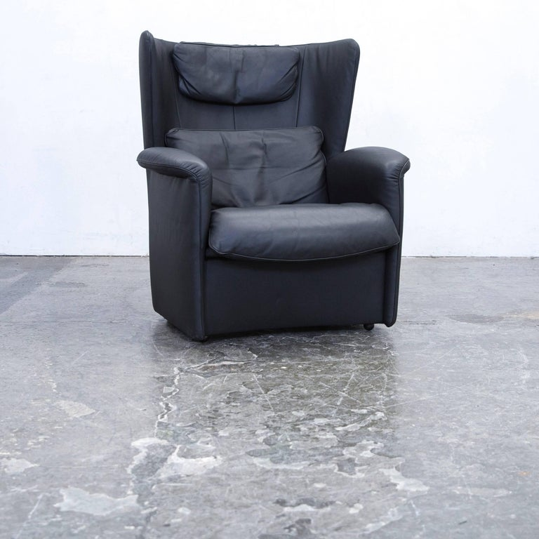 Black colored original De Sede DS 23 designer leather armchair and footrest, in a minimalistic and modern design, made for pure comfort and style.