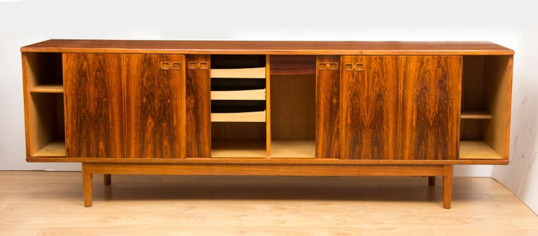 Christian Linneberg rosewood Danish sideboard, circa 1960 with four sliding doors featuring finger pull handles revealing fitted interior.