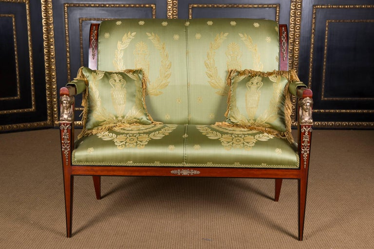 Fine mahogany on massive beech. Fine chiselled Empire fittings and caryatids. High quality upholstery and elegant satin cover. Dimensions: Sofa- Width 108 cm Height 98 cm Depth 65 cm  Armchair- Width 56 cm Height 98 cm Depth 62 cm.