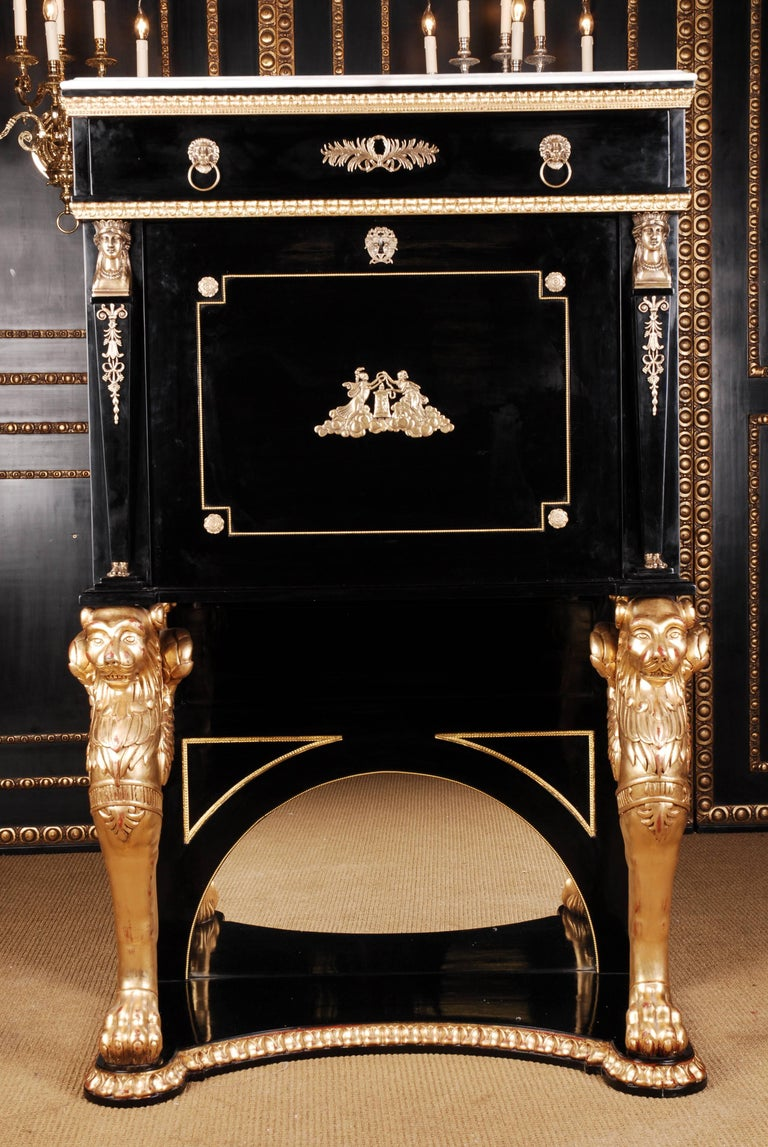 Carved, bent base plate. Two winged, plastically carved. Bole gilded chimera made of solid beechwood arranged on the left and right flush. Behind it is an arched, multi-faceted mirror. The rectangular body with fold-out writing plate is flanked by
