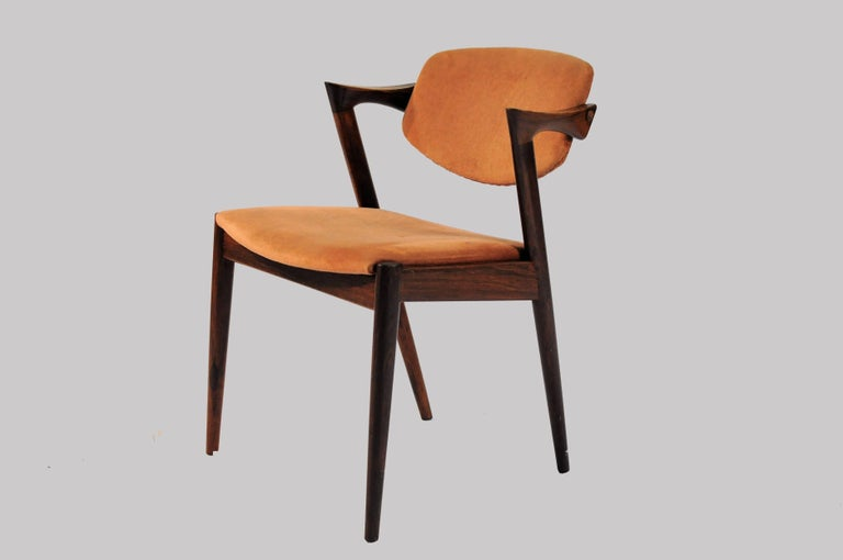 Set of 12 model 42 rosewood dining chairs with adjustable backrest. The chairs will be reupholstered in fabric and color of your choice from Kvadrat within 2 weeks from your choice of color and fabric.  The chairs have Kai Kristiansens typical light