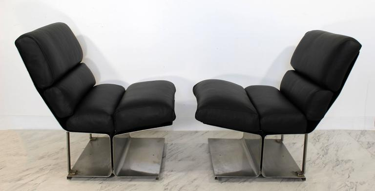 For your consideration is a magnificent pair of steel and black leather hide lounge chairs, by Paul Geoffroy by Uginox, France in the 1970s. Just back from being professionally reupholstered in the finest black leather hide. In excellent condition.