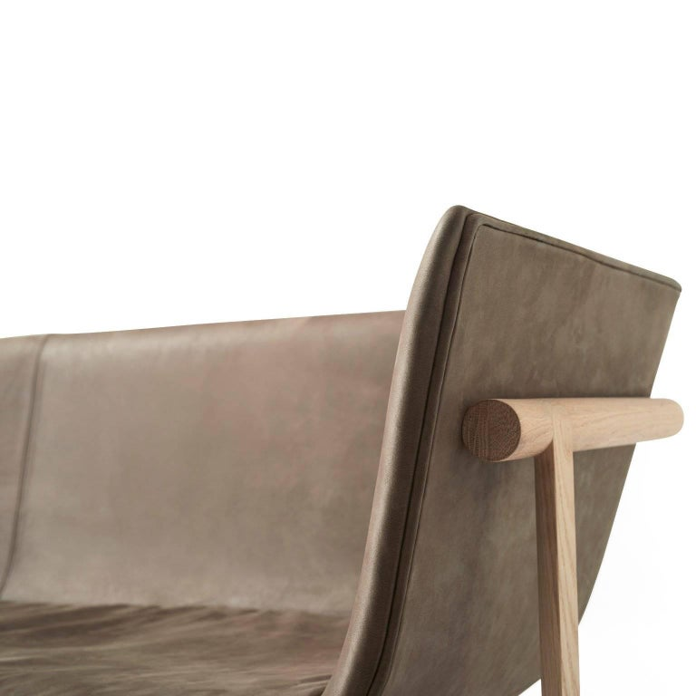 Portuguese designer Rui Alves was inspired to create the Tailor sofa by the memory of his grandfather's favorite tailor shop. An image of the tailors bent over work tables and of old wooden hangers holding grey suits has stayed with Rui. Like that