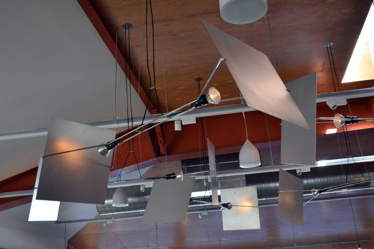 Suspended from the ceiling by wire rope, Pendas is a pared down stainless steel armature supporting two outward facing spotlights. Pivoting aluminum reflectors allow light to be directed up towards the ceiling, or down towards a table. Originally