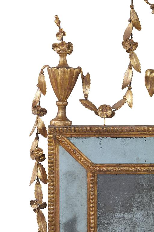 A George III carved giltwood marginal mirror The rectangular central plate within a beaded frame and divided marginal plates, within a beaded outerframe, surmounted by an urn cresting issuing flowerheads and swagged leaves, above stiff leaves and