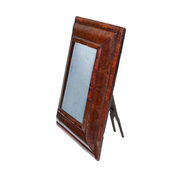 A small William and Mary olivewood oyster veneered mirror The later rectangular bevelled plate within a cushion and moulded frame.