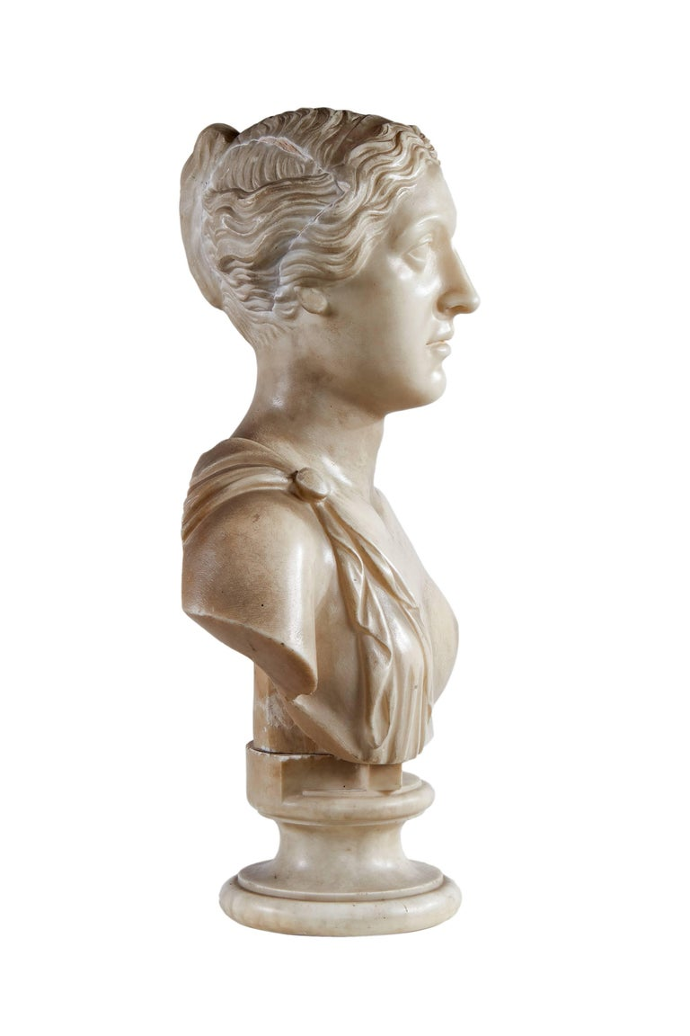 Her hair tied in a chignon, in classical dress revealing one breast, on a turned socle base.