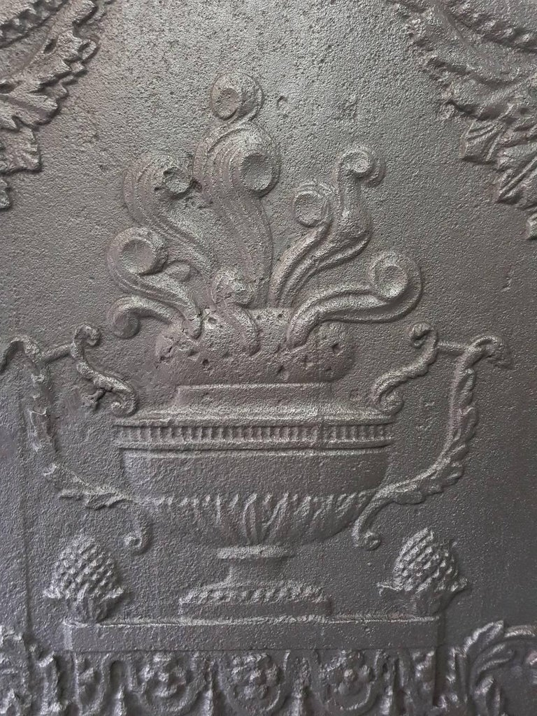 French 19th century cast iron fireback with neoclassical/Louis XVI style decor of a flower basket surrounded by foilage. It has a crack but is welded with bronze a old method for cast iron.  The measurements are, Depth 1.5 cm/ 0.6 inch. Width 62