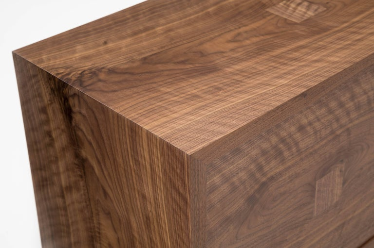 The Marvin credenza is built in our Louisville, KY studio using premium hardwoods and thoughtfully selected wood veneers. The cabinet showcases wide, featured American walnut, with book-matched front doors and waterfall edges. The door pulls are