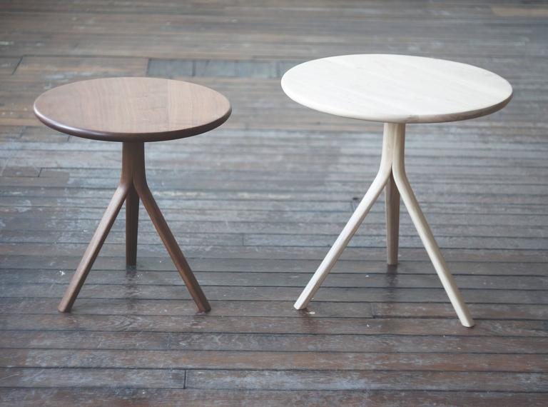 The T07 is a small side or occasional table in solid walnut.  The tripod base structure is formed from three steam bent legs branching out from a central pedestal. The design references the Classic shaker candle stand but with an organic modern