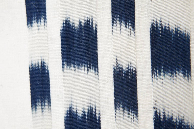 Using a traditional, artisanal weaving technique, this Schumacher Izmir Stripe Ikat is intentionally irregular, emphasizing the art of the hand. Subtle variations are part of its inherent beauty. Featured as oversized decorative accents, these are