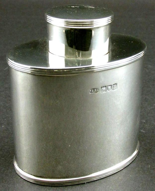 The oval shaped canister decorated with reeded detail to the shoulder and base and fitted with a removable cap, both bearing London hallmarks and date marks for 1908 together with maker's marks for George & Charles Asprey. Inspired by the Georgian