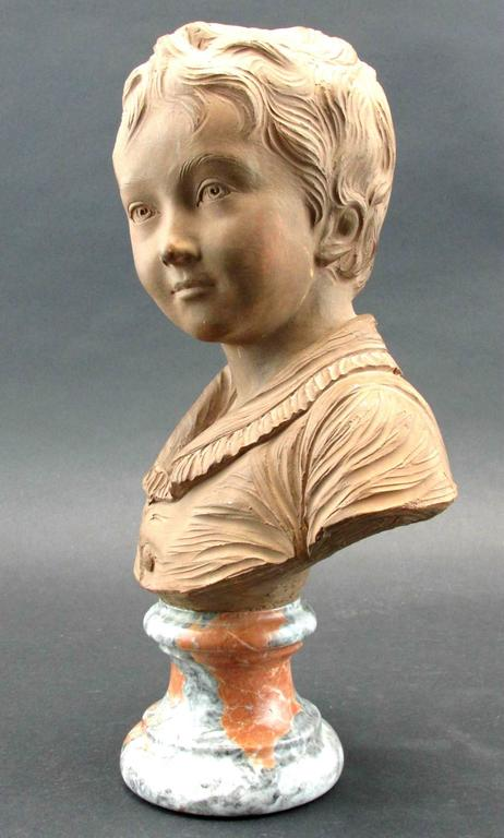 A fine terracotta bust of exacting proportions and exhibiting finely sculpted features, signed in script on the reverse, raised upon a mottled marble socle. Raised atop a mottled marble socle, signed in script on back of shoulder. Height - 14""