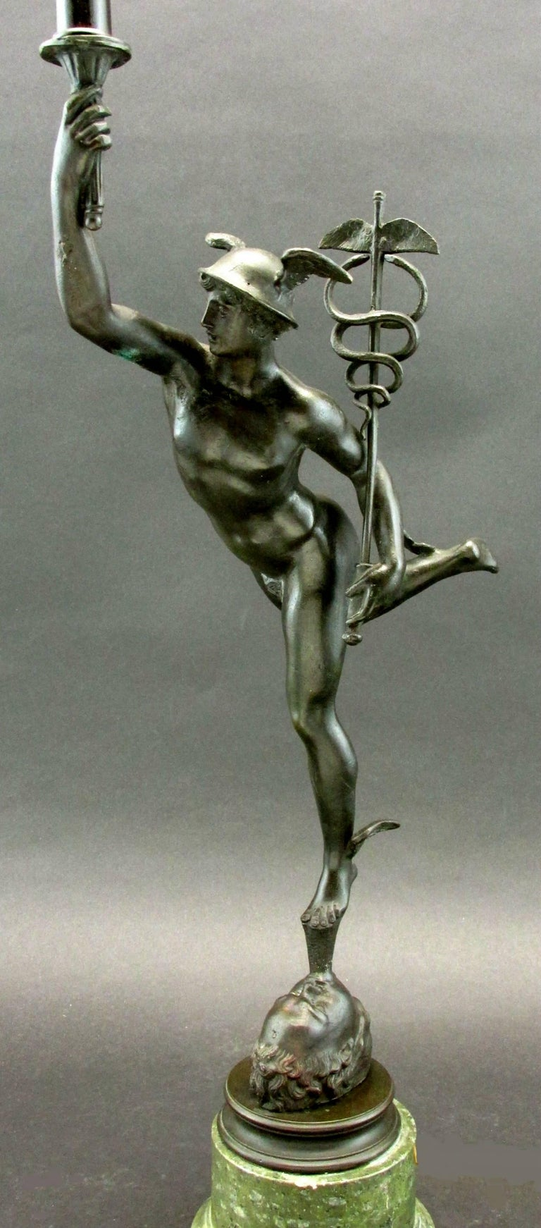 The classical figure of Mercury - (Roman god of abundance & commercial success) shown standing atop the mouth of Aeolus (Ruler of the Four Winds), cradling a caduceus in one hand the other arm outstretched towards the heavens. Exhibiting a black /