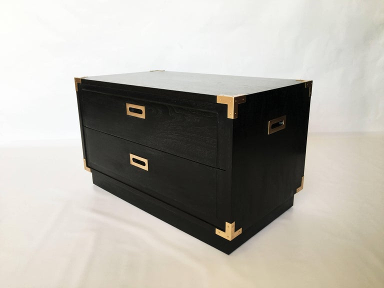 Gorgeous pair of midcentury Campaign style ebonized nightstands/ end tables. Accenting the are copper tone brass corner pieces and hardware. Includes two equal sized drawers, each with recessed pull handles, two recessed handles on either side are