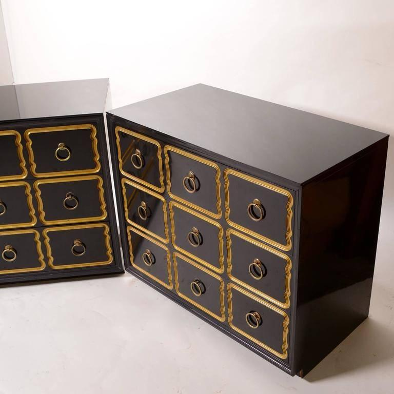 Pair of Dorothy Draper Espana chests / dressers with new black lacquer finish. Large brass ring pulls adorn the centers of the nine wavy gold rimmed drawers.