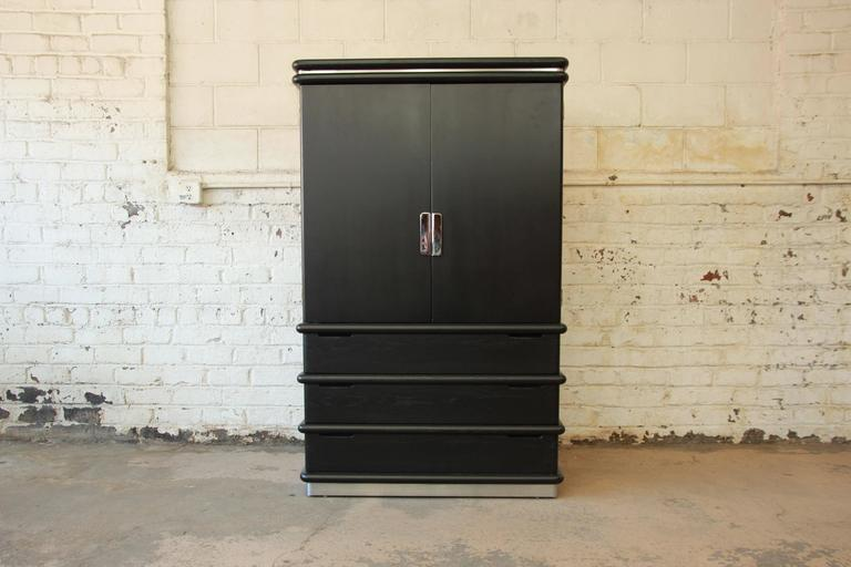 Vintage solid oak and chrome armoire designed by Jay Spectre for Century Furniture. The armoire features an attractive cerused finish in black, as well as carved rounded borders and chrome bands at the top and bottom. The armoire is well constructed