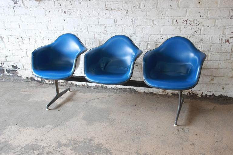 Three tandem shell chairs in original blue leather designed by Charles & Ray Eames in the 1960s. The chairs sit on a metal and aluminium frame with three iconic shells chairs attached. These items were originally seen in airports and offices and now