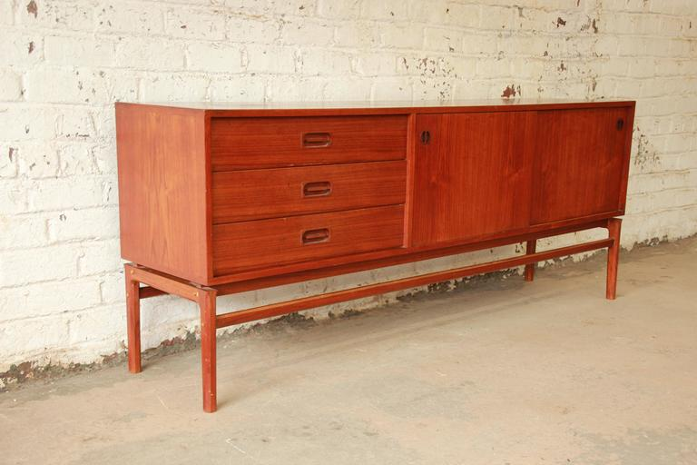 A gorgeous Mid-Century Danish Modern teak long credenza in the manner of Arne Vodder. The credenza features beautiful teak wood grain and sleek Danish Modern design. It offers ample room for storage with three drawers and two sliding doors that