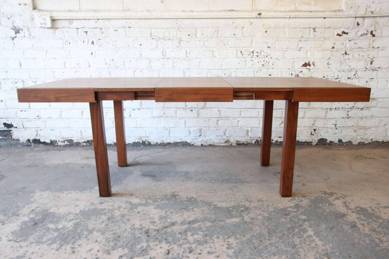 Offering a very nice and refinished extension dining table by George Nelson for Herman Miller. This earlier work of Nelson's has clean geometric lines with a beautiful walnut wood grain. There are two leaves that are stored inside the table and are
