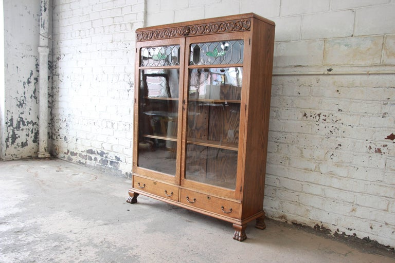 An exceptional antique carved oak bookcase. The bookcase features gorgeous quarter sawn oak wood grain and beautiful leaded stained glass doors. There are nice carved wood details along the top of the bookcase, including a carved face. The case