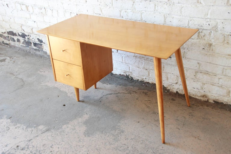 An exceptional Mid-Century Modern desk designed by Paul McCobb for his Planner Group line for Winchedon Furniture. The desk features solid maple wood construction and sleek Minimalist midcentury design. It has a single pedestal with two drawers on
