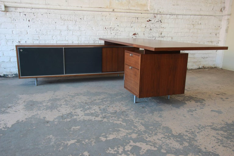 A rare and outstanding Mid-Century Modern L-shaped executive desk designed by George Nelson for Herman Miller. The desk features gorgeous walnut wood grain, with sleek metal feet and hardware. The credenza offers ample room for storage with five