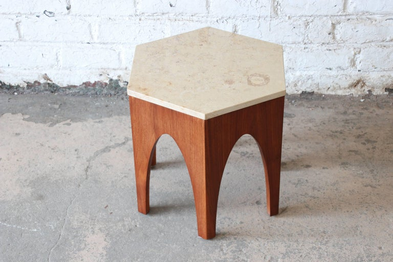 A beautiful Mid-Century Modern hexagon end or occasional table designed by Harvey Probber. The table features an Italian travertine inset top over a sculpted walnut base with Moroccan inspired arches. It is finished on all sides and could also be