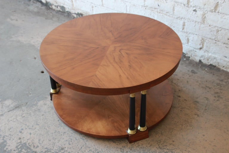 Offering a beautiful and rare round neoclassical coffee table by Baker Furniture Co. The table has a stunning wood grain with three sections of pairs of ebonized columns with solid brass details. The table is fitting for any elegant or traditional