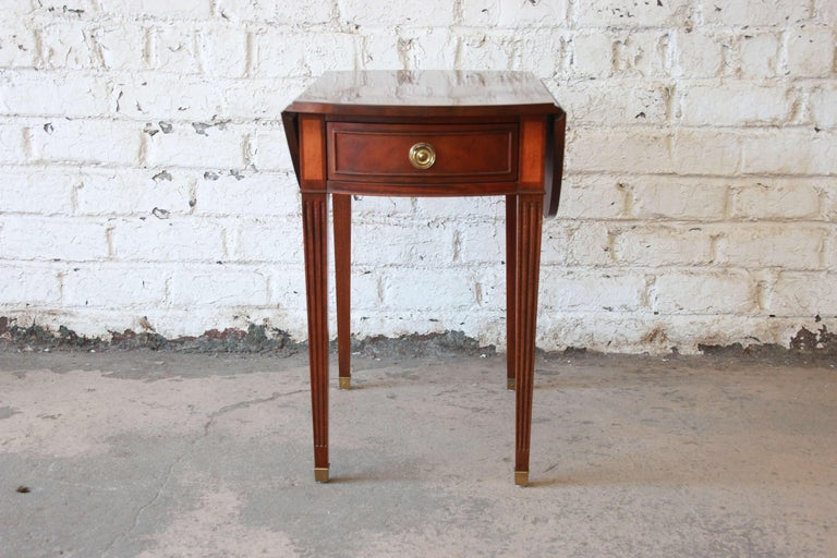 Offering a very nice mahogany and satinwood inlaid drop-leaf side table by Baker Furniture. The table has tapered legs with brass details at the feet. The table has a smooth sliding drawer and round brass pull. Each side has a drop-leaf that