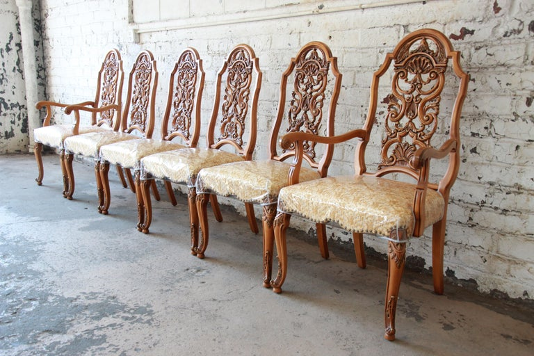 An outstanding set of six ornate French carved dining chairs by Romweber. The set includes two armchairs and four side chairs. The chairs are constructed from solid hardwood with superior quality and the highest attention to detail. The studded
