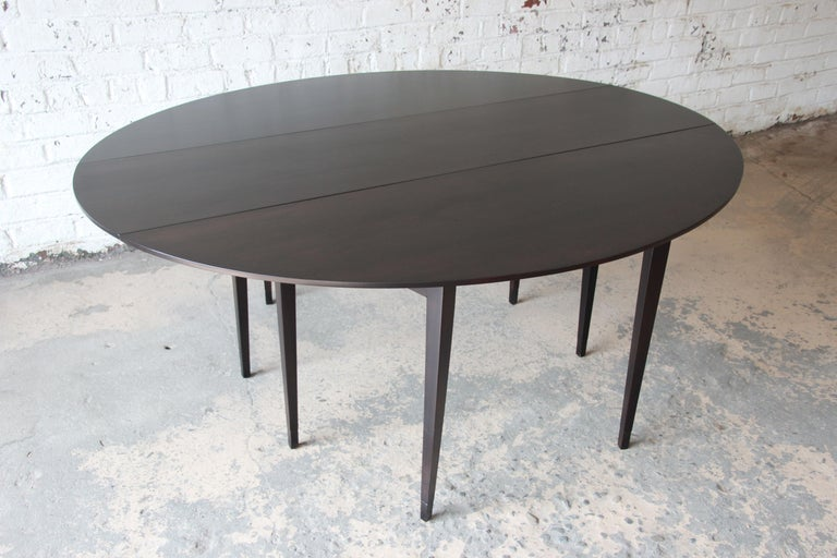 Offering an exceptional Mid-Century Modern drop-leaf dining or console table designed by Edward Wormley for Dunbar Furniture. The table features beautiful dark walnut wood grain and sleek, Minimalist design. Each leg has a nice leather sabot at the