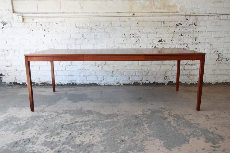 A simple, elegant, walnut Mid-Century Modern extension dining table designed by Florence Knoll. Table includes a 28