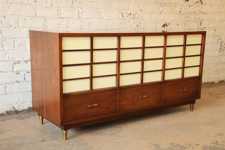 A beautiful Mid-Century Modern nine-drawer dresser or credenza designed by Merton Gershun for American of Martinsville. The dresser features sleek Mid-Century lines, gorgeous walnut wood grain, and a unique design, with white lacquered drawers. The