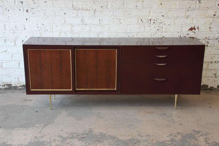 A sleek and stylish Mid-Century Modern credenza or dresser designed by Harvey Probber. The credenza features the original burgundy lacquered case, with sliding rosewood doors. The brass trim and slim brass feet give the credenza a sophisticated and