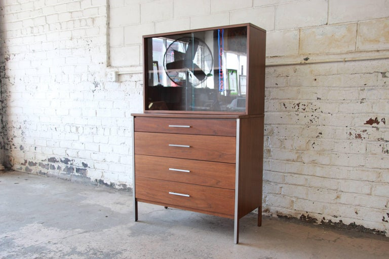 An exceptional Mid-Century Modern four-drawer walnut chest of drawers with glass front hutch top designed by Paul McCobb for Calvin Furniture. The chest features stunning walnut wood grain and sleek, Mid-Century design. The aluminum trim and drawer