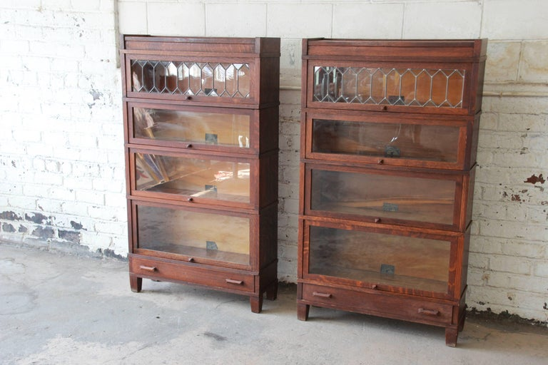 An outstanding pair of antique oak barrister bookcases by Globe-Wernicke.  The bookcases feature - Antique Oak Barrister Bookcases With Leaded Glass Doors By Globe