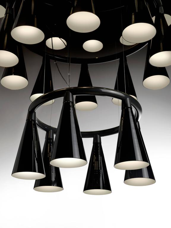 Komori: A chandelier reminiscent of a colony of bats hanging upside down from a tree branch or the ceiling of a cave. Evenly spaced glass shades blown by Murano glass artisans enclose LEDs, and cast their light downwards. Bases can be connected to