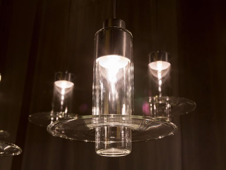 Pawson's design sets one handmade glass cylinder within another, the outer cylinder flaring into a refined disc lip at its lower edge. The lamp casts light downwards, but its clear body also glows along its entire length.  Light source: Bulb G9