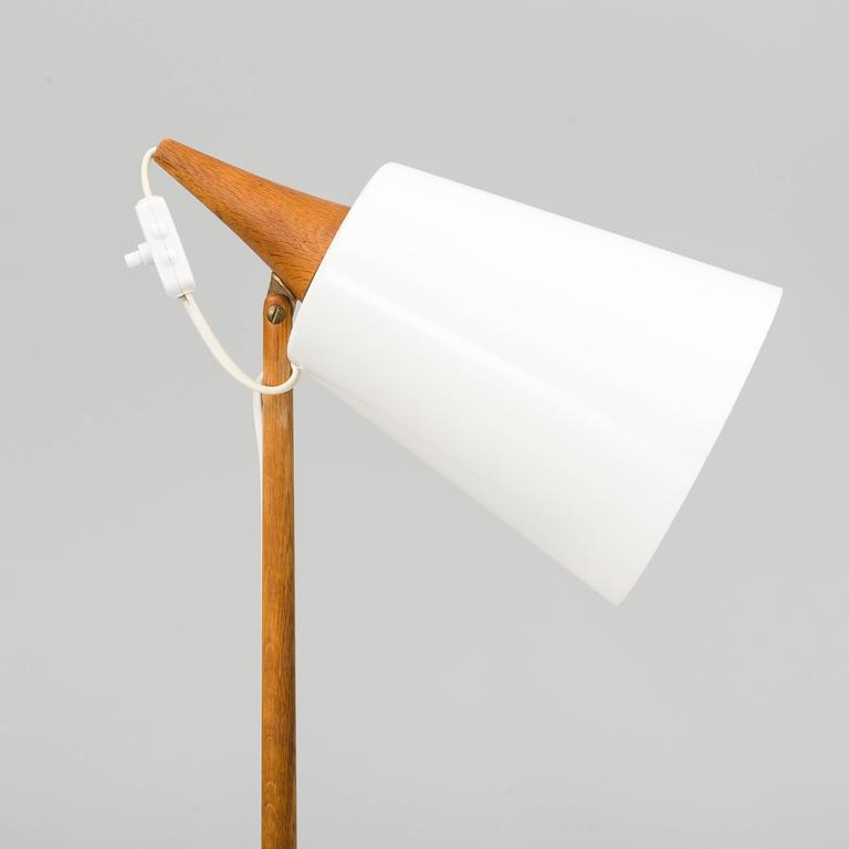 Scandinavian Modern floor lamp by Uno & Osten Kristiansson for Luxus, manufactured in Sweden in 1960s. Natural oak and white acrylic orientable shade. Signed in the bottom.