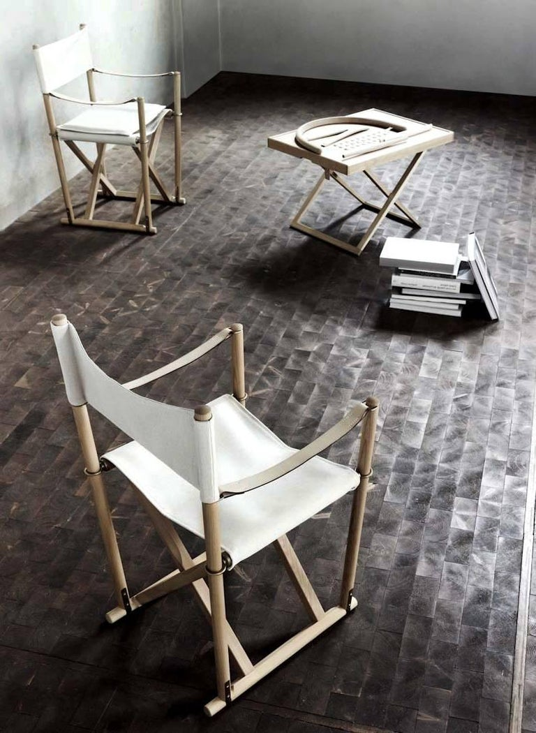 Pair of folding chairs designed by Mogens Koch in 1932 and manufactured by Rud. Rasmussen cabinetmaker in Denmark. Made in natural beech wood and brass. Back, seat and cushions in light canvas. Armrests in full grain leather. Included brass