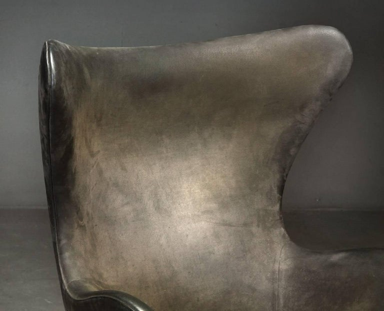 Early easy Egg chair model 3316 designed by Arne Jacobsen and produced by Fritz Hansen in Denmark in 1958. Vintage original upholstery with patinated dark brown/grey Nubuck leather. Tilt function. Signed by Fritz Hansen in the four-star foot.